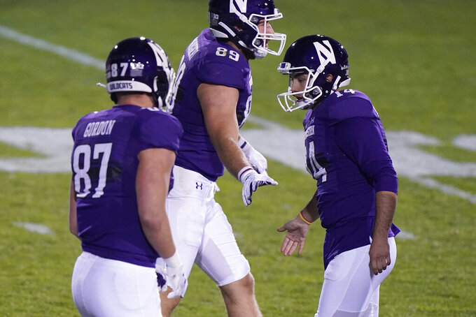 Northwestern kicker Charlie Kuhbander, right, celebrates with tight ends Jack Gordon, left, and Charlie Mangieri after kicking a field goal during the second half of an NCAA college football game against Wisconsin in Evanston, Ill., Saturday, Nov. 21, 2020. Northwestern won 17-7. (AP Photo/Nam Y. Huh)