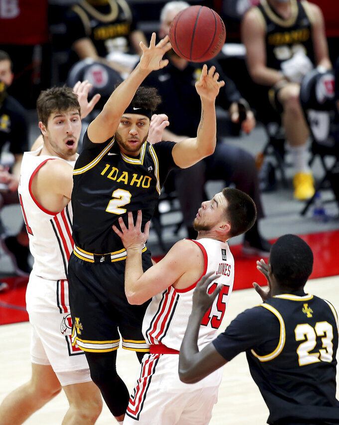 Idaho guard Damen Thacker (2) passes out of a trap by Utah forward Riley Battin (21) and guard Rylan Jones (15) to teammate Idaho forward Babacar Thiombane (23) during an NCAA college basketball game in Salt Lake City, Friday, Dec. 18, 2020. (Scott G Winterton/The Deseret News via AP)