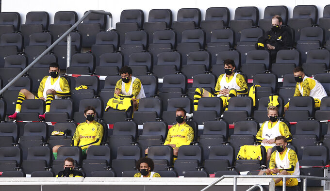 FILE - In this Sunday, May 31, 2020, substitutes for Borussia Dortmund, wearing face masks to protect against coronavirus, look on from the stands during the German Bundesliga soccer match between SC Paderborn 07 and Borussia Dortmund at Benteler Arena in Paderborn, Germany. The German Bundesliga will keep five substitutions for the 2020-21 season because of the coronavirus pandemic. The 36 clubs in the top two German men's soccer leagues voted at a German Football League meeting Thursday, Sept. 3, 2020 to continue the rule for next season. (Lars Baron/Pool via AP, file)