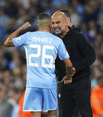 Manchester City's Riyad Mahrez speaks with manager Pep Guardiola on the touchline during the Champions League Group A soccer match between Manchester City and RB Leipzig at the Etihad Stadium, Manchester, England, Wednesday Sept. 15, 2021. (Martin Rickett/PA via AP)