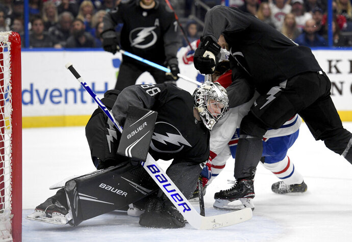 Tampa Bay Lightning goaltender Andrei Vasilevskiy (88) covers the puck during the first period of an NHL hockey game against the Montreal Canadiens, Saturday, Feb. 16, 2019, in Tampa, Fla. (AP Photo/Jason Behnken)