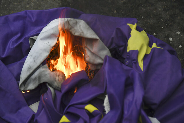 Brexit supporters burn a European Union flag in London, Friday, Jan. 31, 2020. Britain officially leaves the European Union on Friday after a debilitating political period that has bitterly divided the nation since the 2016 Brexit referendum. (AP Photo/Alberto Pezzali)