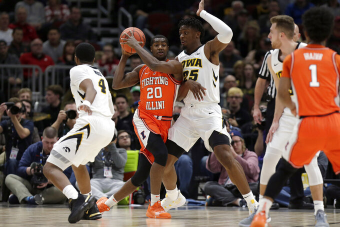 Illinois's Da'Monte Williams (20) looks to pass against Iowa's Tyler Cook (25) during the first half of an NCAA college basketball game in the second round of the Big Ten Conference tournament, Thursday, March 14, 2019, in Chicago. (AP Photo/Kiichiro Sato)
