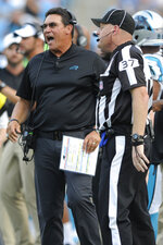 Carolina Panthers head coach Ron Rivera speaks with head linesman Jim Howey (37) during the first half an NFL preseason football game against the Buffalo Bills, Friday, Aug. 16, 2019, in Charlotte, N.C. (AP Photo/Mike McCarn)