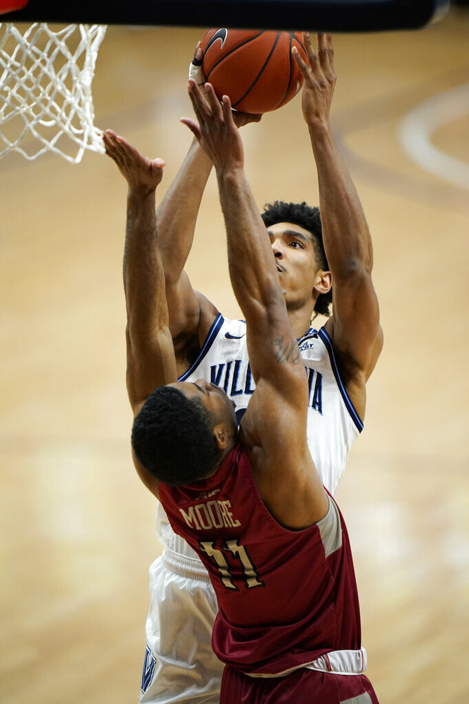 Villanova's Jermaine Samuels, right, goes up for a shot against Saint Joseph's Rahmir Moore during the first half of an NCAA college basketball game, Saturday, Dec. 19, 2020, in Villanova, Pa. (AP Photo/Matt Slocum)