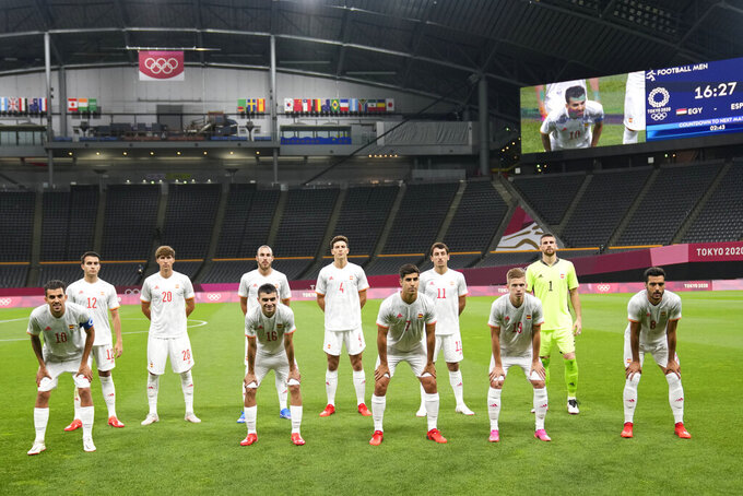 Players of Spain pose for the group photo keeping social distance prior to a men's soccer match against Egypt at the 2020 Summer Olympics, Thursday, July 22, 2021, in Sapporo, Japan. (AP Photo/SIlvia Izquierdo)