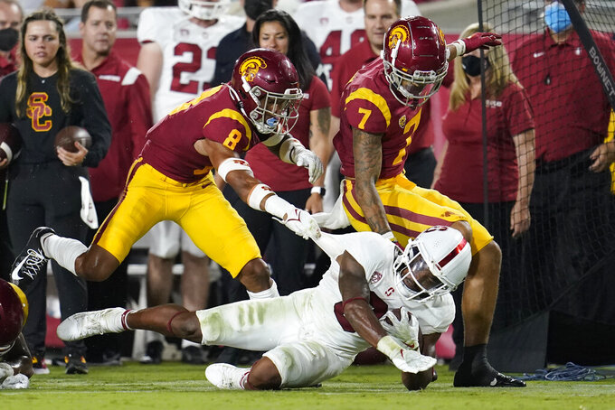 Stanford running back Nathaniel Peat, bottom, is tackled by Southern California cornerback Chris Steele (8) and safety Chase Williams (7) during the second half of an NCAA college football game Saturday, Sept. 11, 2021, in Los Angeles. (AP Photo/Marcio Jose Sanchez)