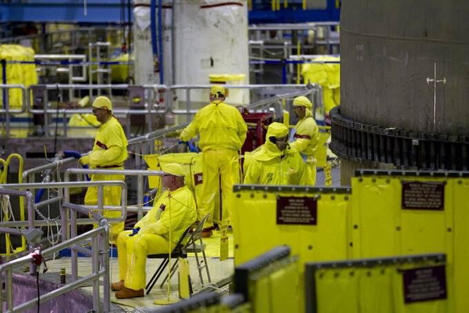 FILE - In this March 25, 2011, file photo, workers gather near the Unit 2 reactor which is undergoing re-fueling during a tour of the Browns Ferry nuclear plant in Athens, Ala. U.S. nuclear plants will be allowed to keep workers on longer shifts to deal with staffing problems in the coronavirus pandemic. Nuclear Regulatory Commission officials outlined the temporary shift extensions to nuclear power officials on Thursday, April 2, 2020. (AP Photo/Dave Martin, File)