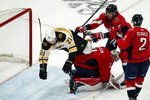 Boston Bruins left wing Nick Ritchie (21) falls over Washington Capitals goaltender Craig Anderson (31) with Capitals defenseman Brenden Dillon (4) nearby, during the second period of Game 1 of an NHL hockey Stanley Cup first-round playoff series Saturday, May 15, 2021, in Washington. (AP Photo/Alex Brandon)