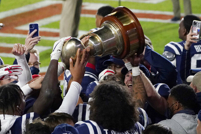 Mississippi players hoist the Egg Bowl trophy as they celebrate a win over Mississippi State in an NCAA college football game Saturday, Nov. 28, 2020, in Oxford, Miss. The (AP Photo/Rogelio V. Solis)