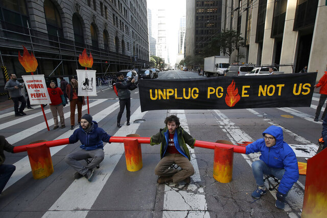 Protesters block traffic on Beale Street where a Pacific Gas & Electric building is located in San Francisco, Monday, Dec. 16, 2019. Pacific Gas & Electric will have to quickly reshuffle its board of directors and redraw a complex plan addressing more than $50 billion in potential wildfire claims to gain Gov. Gavin Newsom's support in time to meet a fast-approaching deadline to emerge from bankruptcy protection. (AP Photo/Jeff Chiu)