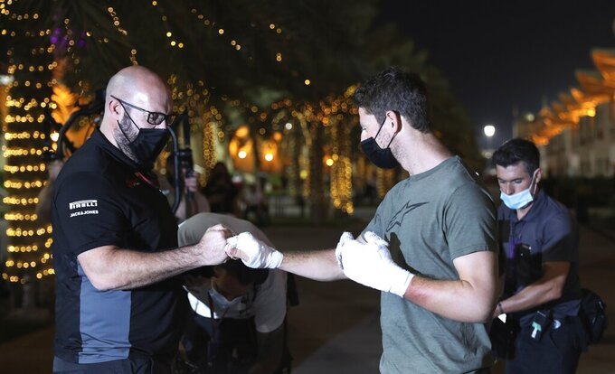 Haas driver Romain Grosjean of France, right, shares a fist bumps after his arrival to paddock to thank the marshals Thursday, Dec. 3, 2020, in Bahrain International Circuit in Sakhir, Bahrain.  Grosjean escaped with only minor burns when his Haas car exploded into a fireball after crashing on the first lap at last weekend's Bahrain GP. (AP Photo/Kamran Jebreili)