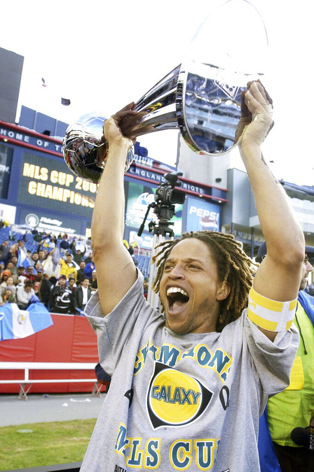 FILE - Los Angeles Galaxy captain Cobi Jones shouts as he holds the MLS Cup aloft after they defeated the New England Revolution, 1-0, in overtime at Gillette Stadium in Foxboro, Mass., in this Sunday Oct. 20, 2002, file photo. Jones, one of the league's original players who spent his entire 11-year career with the Galaxy, was named one of the MLS 25 Greatest on Wednesday, Dec. 9, 2020. His favorite moment in his 11 MLS seasons is winning that first league title with the Galaxy. (AP Photo/Elise Amendola, File)