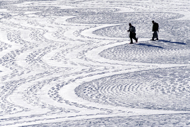 In this photo taken Jan. 7, 2020, British artist Simon Beck, left, and a volunteer put the final touches on a geometrical snow drawing on a frozen reservoir near Silverthorne, Colo. Beck says he hopes his art makes people more aware of the beauty of the environment. (AP Photo/Thomas Peipert)