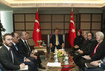 New Zealand's Deputy Prime Minister Winston Peters, third from right, is flanked by two New Zealander officials wearing Islamic headscarves during a meeting with Turkey's President Recep Tayyip Erdogan, center, in Istanbul, Friday, March 22, 2019. An emergency meeting of the organization of Islamic Conference was held in Istanbul in Turkey after a gunman killed 50 people in two mosques in the South Pacific nation. New Zealand's Ambassador to Turkey, Wendy Hinton, is at the right.(Presidential Press Service via AP, Pool)