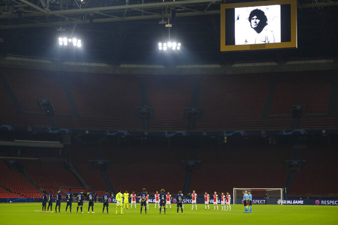 """Ajax players, wearing black mourning arm bands, Midtjylland players and the referee and linesmen observe a minute of silence as they commemorate Argentinian soccer great Diego Maradona, picture seen above, prior to the group D Champions League soccer match between Ajax and Midtjylland at the Johan Cruyff ArenA in Amsterdam, Netherlands, Wednesday, Nov. 25, 2020. Maradona, who scored the """"Hand of God"""" goal in 1986 and led his country to that year's World Cup title before later struggling with cocaine use and obesity, has died. He was 60. (AP Photo/Patrick Post)"""