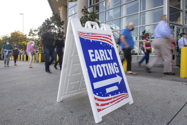 Long lines of people wrap around the Smoothie King Center in New Orleans on Monday, Oct. 26, 2020, for one of the last days of early voting. (Chris Granger/The Advocate via AP)