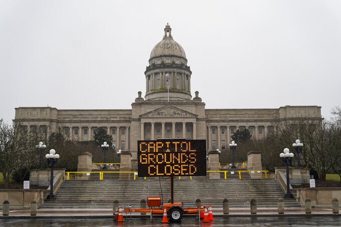 A sign displayed outside the Capitol building in Frankfort, Ky., advises that the grounds are closed, Sunday, Jan. 17, 2021. Some state capitols are closed, fences are up and extra police are in place at statehouses across the U.S. as authorities brace for potentially violent demonstrations over the coming days. (AP Photo/Bryan Woolston)