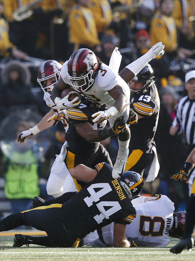 Minnesota running back Cam Wiley, top, leaps over Iowa defensive back Devonte Young, center, and linebacker Seth Benson, bottom, during the first half of an NCAA college football game, Saturday, Nov. 16, 2019, in Iowa City, Iowa. (AP Photo/Matthew Putney)