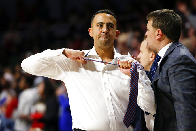 South Alabama head coach Richie Riley rips off his tie after a call during the first half of an NCAA college basketball game against Auburn, Tuesday, Nov. 12, 2019, in Mobile, Ala. (AP Photo/Butch Dill)