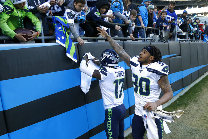 Seattle Seahawks wide receiver Malik Turner (17) and strong safety Bradley McDougald (30) celebrate with fans following an NFL football game against the Carolina Panthers in Charlotte, N.C., Sunday, Dec. 15, 2019. (AP Photo/Brian Blanco)