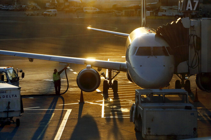 FILE - In this Dec. 8, 2018, file photo a worker fuels a Delta Connection regional airlines passenger jet at Logan International Airport in Boston. More than 7 in 10 U.S. airline passengers (72%) say ticket price is a key deciding factor when choosing an airport to fly into or from, according to a 2019 survey commissioned by NerdWallet and conducted online by The Harris Poll among more than 1,800 U.S. adults who have ever flown on an airplane. (AP Photo/Bill Sikes)