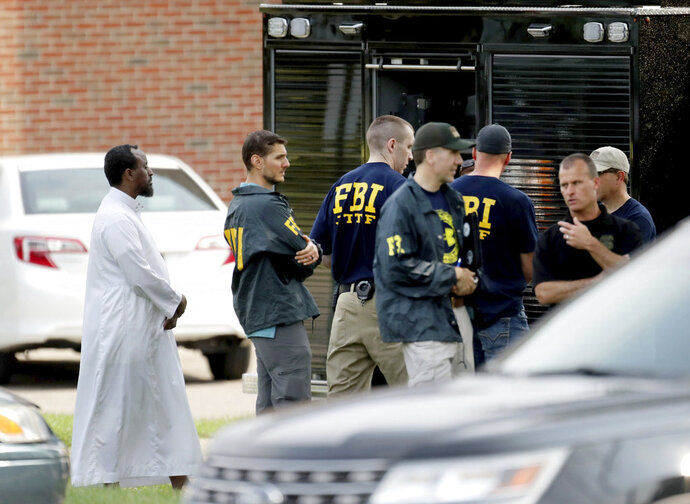 FILE - In this Aug. 15, 2017 file photo, Law enforcement officials investigate an explosion at the Dar Al-Farooq Islamic Center in Bloomington, Minn. Federal authorities said Tuesday, March 13, 2018, they have charged three men from rural central Illinois with the bombing of a Minnesota mosque last year and one of the men told an investigator the goal of the attack was to