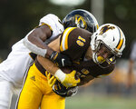 Missouri safety Ronnell Perkins, left, tackles Wyoming wide receiver Ayden Eberhardt during the second quarter of an NCAA college football game Saturday, Aug. 31, 2019, in Laramie, Wy. (AP Photo/Michael Smith)