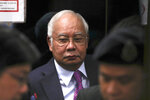 FILE - In this June 18, 2019, file photo, former Malaysian Prime Minister Najib Razak walks into lift as he arrives at Kuala Lumpur High Court in Kuala Lumpur, Malaysia. The second trial of Malaysian's ex-Prime Minister Najib linked to the multibillion-dollar looting of the 1MDB state investment fund was delayed Monday, Aug. 19, by a week to allow his first trial to end.(AP Photo/Vincent Thian, File)