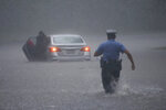 A Philadelphia police officer rushes to help a stranded motorist during Tropical Storm Isaias, Tuesday, Aug. 4, 2020, in Philadelphia. The storm spawned tornadoes and dumped rain during an inland march up the U.S. East Coast after making landfall as a hurricane along the North Carolina coast. (AP Photo/Matt Slocum)