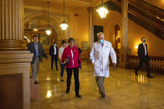Kansas Gov. Laura Kelly walks to a news conference with Lee Norman, secretary of Kansas Department of Health and Environment, to give updates regarding the COVID-19 delta variant Wednesday, July 28, 2021 at the Statehouse in Topeka, Kan. Democratic Gov. Laura Kelly on Wednesday issued a new mandate for Kansas residents to wear masks in indoor public spaces even if they've been vaccinated against COVID-19, though there's a good chance she won't be able to make it stick in many places. (Evert Nelson/The Topeka Capital-Journal via AP)