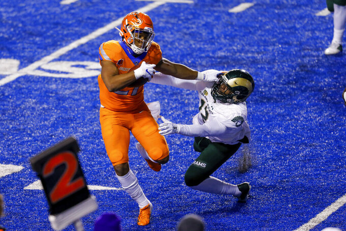 Boise State running back Andrew Van Buren (21) stiff-arms Colorado State linebacker Cam'ron Carter (12) on a run during the first half of an NCAA college football game Thursday, Nov. 12, 2020, in Boise, Idaho. (AP Photo/Steve Conner)