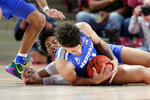 Memphis guard Lester Quinones, front, gets the loose ball in front of Houston guard Nate Hinton, back, during the first half of an NCAA college basketball game Sunday, March 8, 2020, in Houston. (AP Photo/Michael Wyke)