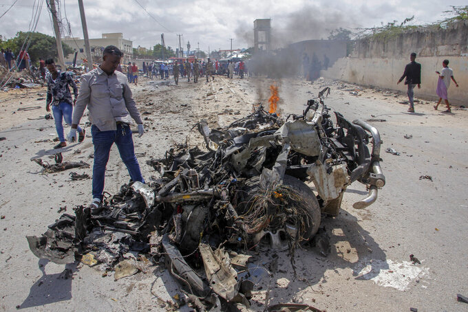 Security forces and civilians gather near the wreckage after a suicide car bomb attack that targeted the city's police commissioner in Mogadishu, Somalia Saturday, July 10, 2021. At least nine people are dead and others wounded after the large explosion, a health official at the Medina hospital said, noting that the toll reflected only the dead and wounded brought there. (AP Photo/Farah Abdi Warsameh)