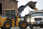 In this Sunday, Dec. 1, 2019 photo, a front end loader dumps salt into a waiting truck, as others line up in preparation for a snow storm at the DPW yard in Worcester, Mass. A wintry storm that made Thanksgiving travel miserable across much of the country gripped the East with a messy mixture of rain, snow, sleet and wind.  (Christine Peterson/Worcester Telegram & Gazette via AP)