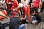 Lebanese Red Cross volunteers help an injured of Hezbollah supporters during clash with Lebanese riot policemen during a protest in Beirut, Lebanon, Friday, Oct. 25, 2019. Leader of Lebanon's Hezbollah calls on his supporters to leave the protests to avoid friction and seek dialogue instead. (AP Photo/Hassan Ammar)