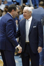 Duke head coach Mike Krzyzewski, left, and North Carolina head coach Roy Williams speak prior to an NCAA college basketball game in Chapel Hill, N.C., Saturday, Feb. 8, 2020. (AP Photo/Gerry Broome)