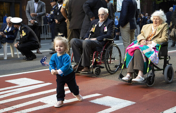 A girl runs with a flag ahead of the Anzac Day parade in Sydney, Australia, Sunday, April 25, 2021. Australians and New Zealanders paid tribute to their war dead Sunday as both nations prepared to withdraw from their longest war in Afghanistan. (AP Photo/Mark Baker)