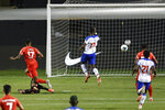 Canada's Cyle Larin (17) scores past Haiti's Josue Duverger, bottom left, during the second half of a World Cup qualifying soccer match Tuesday, June 15, 2021, in Bridgeview, Ill. (AP Photo/Kamil Krzaczynski)