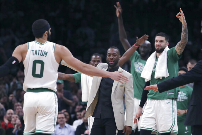 Boston Celtics guard Kemba Walker, in jacket, congratulates forward Jayson Tatum (0), who had hit a 3-point shot late in the fourth quarter of the team's NBA basketball game against the Orlando Magic in Boston, Wednesday, Feb. 5, 2020. (AP Photo/Charles Krupa)