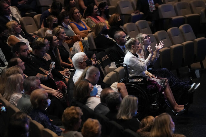 Angela Gonzalez, second from right, and daughter Deven, right, attend in wheelchairs due to their injuries, during the funeral service for their late husband and father Edgar Gonzalez, 44, who was killed last month in the Champlain Towers South condominium collapse, on Friday, July 23, 2021, at Christ Fellowship church in Palmetto Bay, Fla. Angela and Deven were injured but survived the collapse, falling multiple stories.(AP Photo/Rebecca Blackwell)