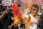 FILE - In this June 18, 2019, file photo, a protester burns a mock Chinese flags at Manila's Rizal park, Philippines, to condemn a recent incident that involved a Chinese fishing vessel hitting a Filipino fishing boat. The Philippine Defense Secretary Delfin Lorenzana raised the sinking of the Philippine fishing boat by a Chinese trawler in the South China Sea in a meeting with Southeast Asian counterparts. (AP Photo/Aaron Favila, File)