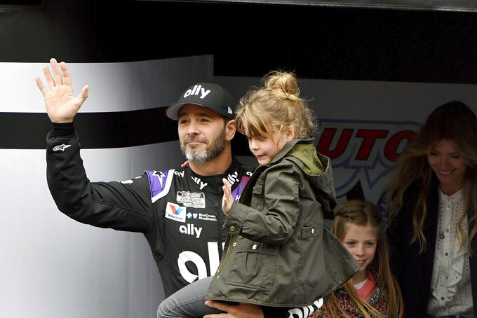FILE - In this March 1, 2020, file photo, Jimmie Johnson is introduced to the crowd during activities as he carries his youngest daughter Lydia as his oldest daughter Genevieve and wife Chandra follow prior to a NASCAR Cup Series auto race in Fontana, Calif. This year has hardly been the farewell tour Jimmie Johnson envisioned when he said 2020 would be his final season of full-time NASCAR racing. The seven-time champion has had to say his goodbyes at empty race tracks absent of all fanfare and now his streak of 663 consecutive races has ended because Johnson tested positive for the coronavirus. (AP Photo/Will Lester, File)