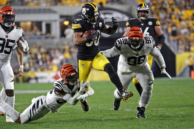 Pittsburgh Steelers running back James Conner (30) is tackled by Cincinnati Bengals free safety Jessie Bates (30) during the second half of an NFL football game in Pittsburgh, Monday, Sept. 30, 2019. (AP Photo/Don Wright)