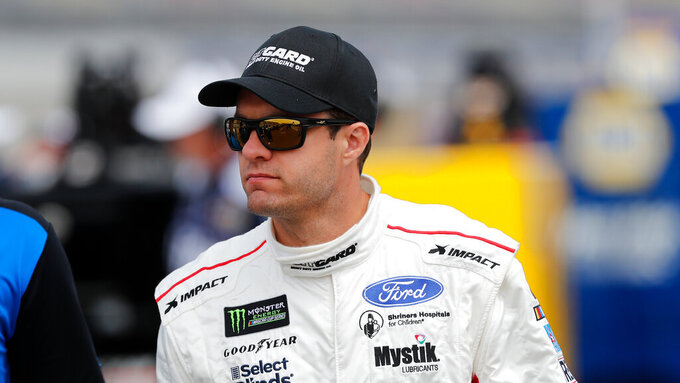 David Ragan walks to his car before qualifying for the NASCAR cup series race at Michigan International Speedway, Saturday, June 8, 2019, in Brooklyn, Mich. (AP Photo/Carlos Osorio)