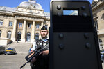 A police officer stands behind a shield outside the Paris courthouse Thursday, Sept. 2 2021. In an enormous custom-designed chamber, France is putting on trial 20 men accused in the Nov. 13, 2015, Islamic State terror attacks on Paris that left 130 people dead and hundreds injured. Nine gunmen and suicide bombers struck within minutes of each other at the national soccer stadium, the Bataclan concert hall and restaurants and cafes. Salah Abdeslam, the lone survivor of the terror cell from that night is among those being tried for the deadliest attack in France since World War II. (AP Photo/Francois Mori)
