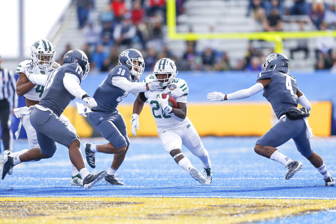 Ohio running back O'Shaan Allison, center, runs with the ball as Nevada defensive back Christian Swint (38) reaches across his face guard and Nevada defensive backs Jordan Lee, left, and EJ Muhammad, right, close in for the tackle in the first half of the Famous Idaho Potato Bowl NCAA college football game Friday, Jan. 3, 2020, in Boise, Idaho. (AP Photo/Steve Conner)