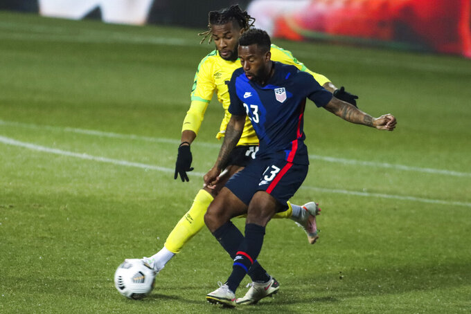 USA's Kellyn Acosta, foreground, duels for the ball with Jamaica's Kasey Palmer during  the international friendly soccer match between USA and Jamaica at SC Wiener Neustadt stadium in Wiener Neustadt, Austria, Thursday, March 25, 2021. (AP Photo/Ronald Zak)