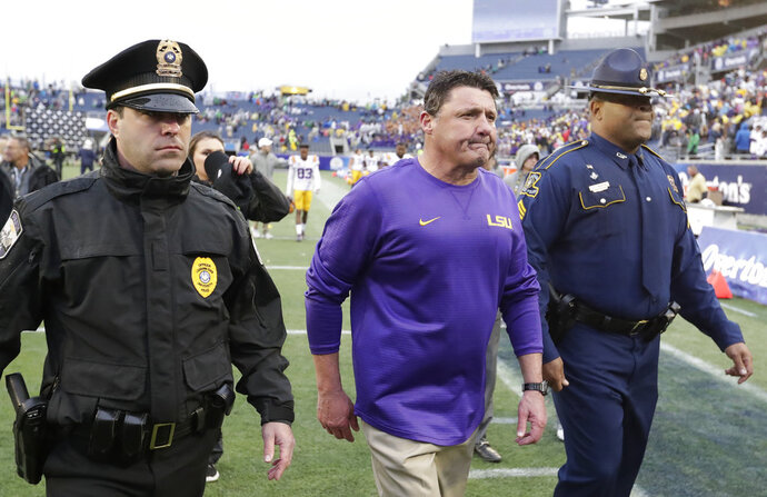 FILE - In this Jan. 1, 2018, file photo, LSU head coach Ed Orgeron, center, leaves the field after losing the Citrus Bowl NCAA college football game against Notre Dame, 21-17, in Orlando, Fla. Orgeron has a little explaining to do _ namely, why he demoted Steve Ensminger in the first place. Ensminger is being re-introduced on Thursday as LSU's offensive coordinator, a post he held on an interim basis in 2016 before Orgeron's failed attempt to wed recently jettisoned coordinator Matt Canada's distinctive style with the Tigers' talent base. (AP Photo/John Raoux, File)