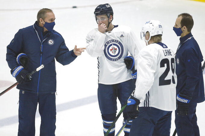 Winnipeg Jets head coach Paul Maurice, left, talks to Neal Pionk (4) and Patrik Laine (29) during their NHL hockey training camp practice in Winnipeg, Manitoba, Wednesday, Jan. 6, 2021. (John Woods/The Canadian Press via AP)